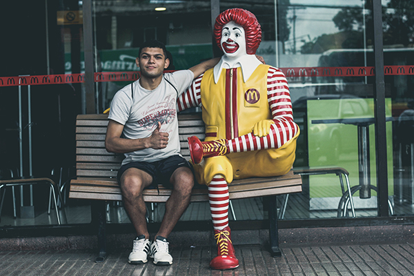 man sitting with mcdonalds statue